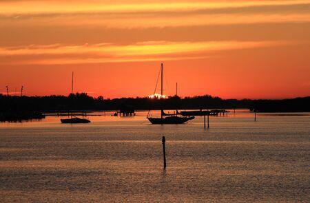 Early morning sailing in Sarasota, Florida.  Boats anchored on the bay at sunrise. Stock Photo