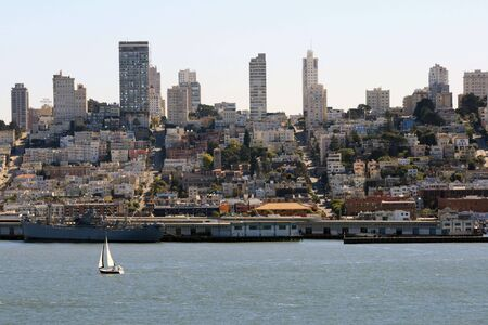 A sailboat sails in front of a beautiful San Francisco skyline.