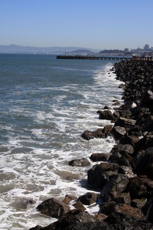 Waves splash onto the rocks in beautiful San Francisco.  A fishing pier can be seen in the background.