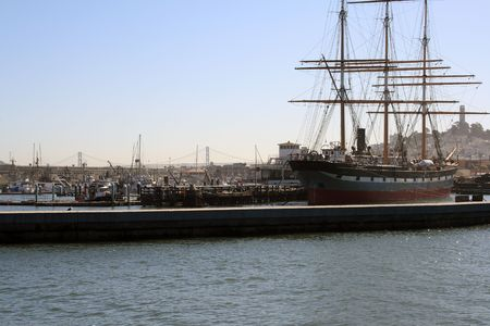 Grand ship at San Francisco Maritime Museum.  Coit Tower and the Bay Bridge can be seen in backdrop. Stock Photo