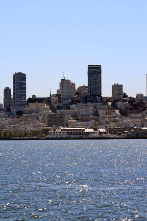View of the city from San Francisco Bay.  Colorful buildings and hilly streets can be seen on this sunny day.