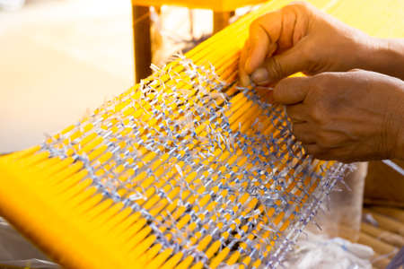 A Skillful Lady is Binding Mai Thai or Thai Silk for Making a Pattern  by using Plastic Rope