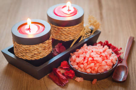 Pink spa salts for body scrub and aromatic candles and dried flowers