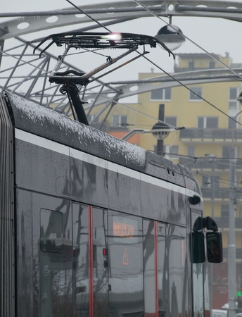 electric avenue: Tram taxiing on the final stop during a complete lockout tramway traffic caused by calamity toothfish. On pantographs the tram at the contact point with frosted trolleys are visible electrical discharge and flying sparks. Stock Photo
