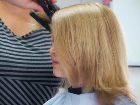 Blond girl  at the hair salon during hair ironing photo