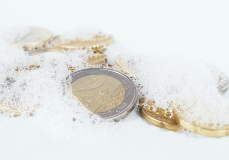illegality: Euro coins in white soapy foam