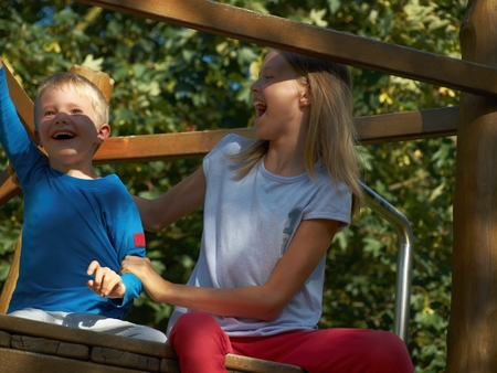 family units: Happy siblings are smiling on the climbing frame Stock Photo