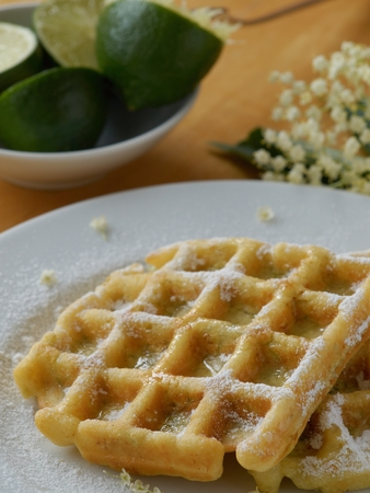 Waffles with elderflower, topped with powder sugar and lime juice