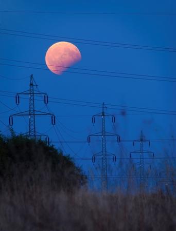Partial lunar eclipse above a electricity pylons at dusk.