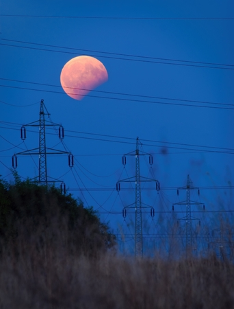 three generations: Partial lunar eclipse above a electricity pylons at dusk.