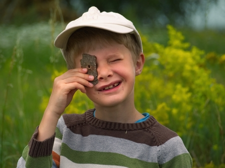 Little boy in a baseball cap looks through a hole in the bark of a tree Stock Photo