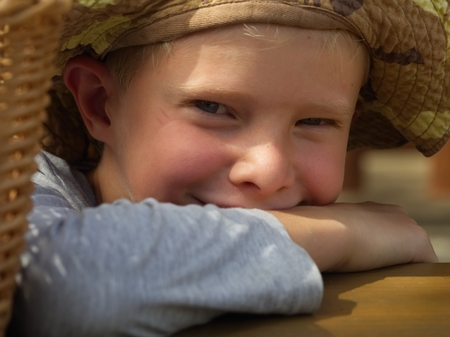 Close up of smiling little boy in an outdoor hat rests on a wooden table where a wicker basket is laid.