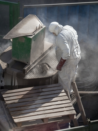 A worker is working  in the dust clouds with a machine for the production of a cement mix for sanitation of the sewer shaft. Stock Photo