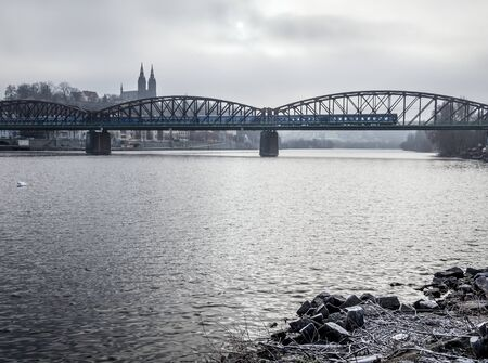 Old railway bridge over the Vltava river in Prague with passing train in winter foggy day.