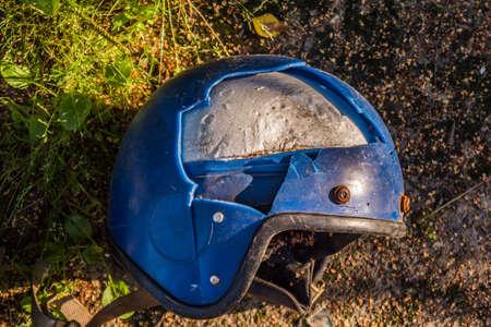 Un viejo casco de moto roto en el suelo
