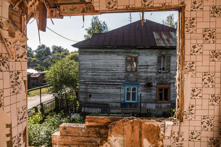 Old ruined wooden house. Two-story building intended for demolition. Summer day Reklamní fotografie