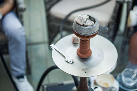 Beautiful new hookah on the table on the summer terrace. Hookah Russian production. Summer day