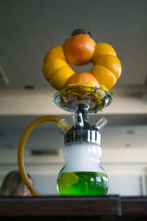 Beautiful glass hookah, with a fruit bowl, consisting of oranges and grapefruit. Handmade in a flask green syrup and lemons