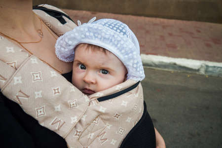 A small child in a children's backpack with mom. Half a year old baby. Walk down the street. Summer day