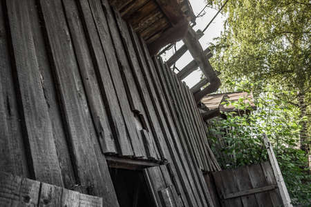 Old ruined wooden house. Two-story building intended for demolition. Summer day 写真素材