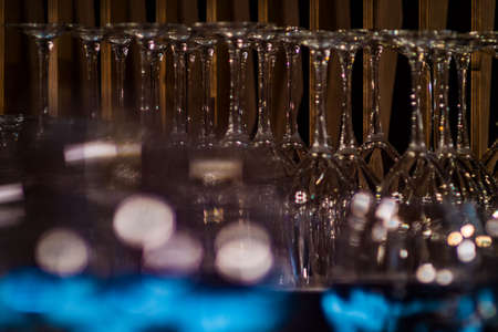 Glass wine glasses in the restaurant. Several rows of empty wine glasses. Cafe Bar
