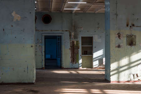 Old abandoned building of the Soviet manufactory. Empty room with columns. Daylight