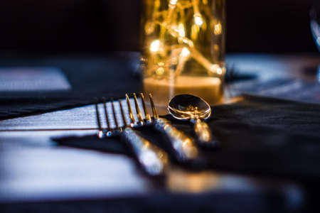 Two forks and a spoon on a table in a restaurant. Table setting before serving. Dark room