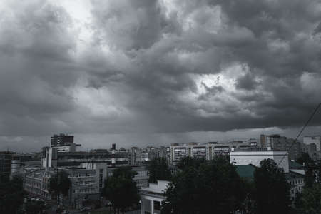 Storm clouds in the sky over the city. Gray gloomy sky before hurricane