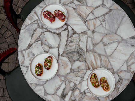 Delicious bruschetta with a variety of fillings. On a white plate with sauce