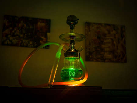 Beautiful glass hookah on the table in the bar. Bright lights Imagens