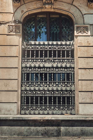 Old window with a beautiful iron bars on a house in a small European city. Day Imagens