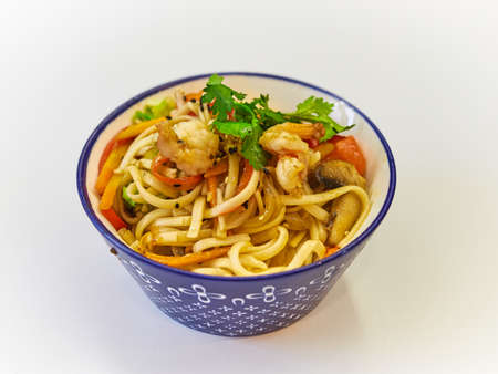 Udon noodles with seafood in a plate on a white surface. 版權商用圖片