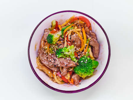 Udon noodles with meat in a plate on a white surface.