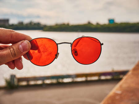 Old red sunglasses in hand. Scratched glass. Day 版權商用圖片