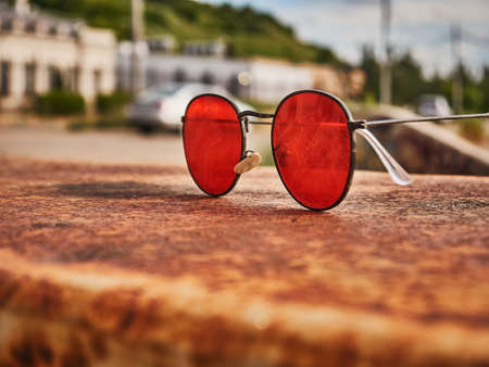 Old red sunglasses on a concrete surface. Scratched glass. Day