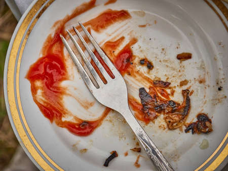 Empty plate with traces of ketchup and meat, fork on top.