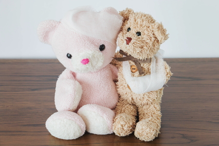 contusion: Teddy bear and friend with trauma of the head and trauma of the bandaged arm Stock Photo