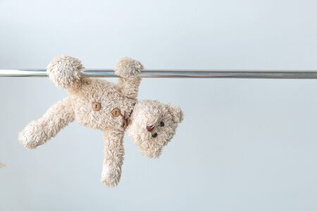 little teddy bear hang the bar by his hand to exercise at out door playground