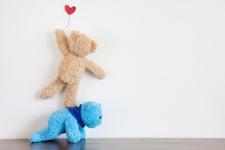 Two teddy bear are love,Teddy bear trying catch red heart balloon
