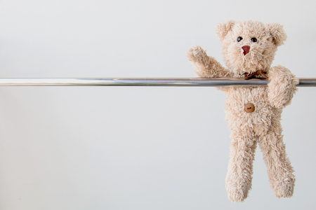 Cute teddy bear hanging on steel rail ,Teddy bear exercise for fit and firm. Stock Photo