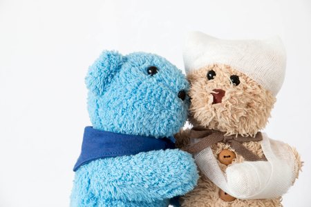 Teddy bear with trauma of the head and bandaged arm ,Young teddy bear nurse is taking care of lover