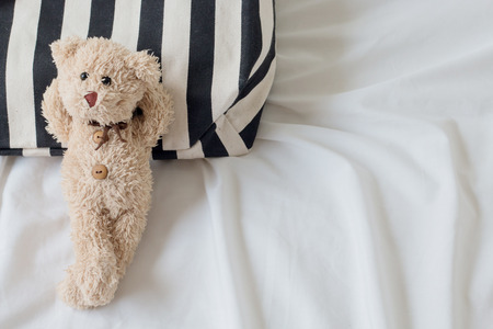 bed sheet: top view of teddy bear is relaxing on black&white fabric a bed background , Relaxing concept Stock Photo