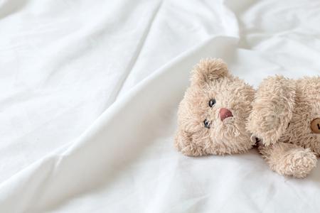 Cute little teddy bear is sleeping in the bed on white blanket,Teddy bear is relaxing