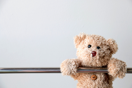 Cute teddy bear hanging on steel rail ,Teddy bear exercise for fit and firm. Banco de Imagens