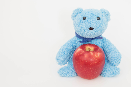 he: Cute teddy bear with red apple fruit .He is strong ,Health care and diet concept