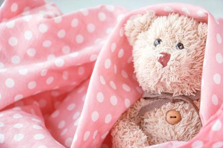 Cute little teddy bear is sleeping in the bed on pink blanket,Teddy bear is relaxing Stock Photo