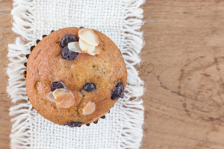 Yummy banana cupcake with whole grain on wood background