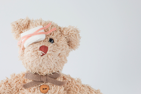 Teddy bear is playful and got accident so he applying medical and injured eyes using  bandage. Stok Fotoğraf