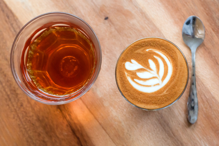 A Cup of  latte art coffee and Hot tea on wood background Banco de Imagens