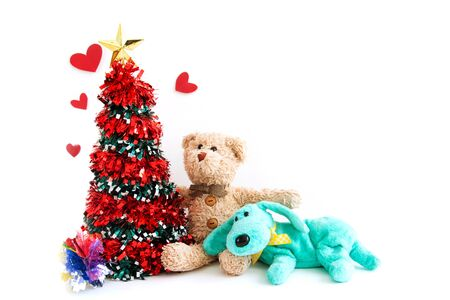 Christmas tree with a teddy bear and cute puppy are happy feels in New year. Stockfoto